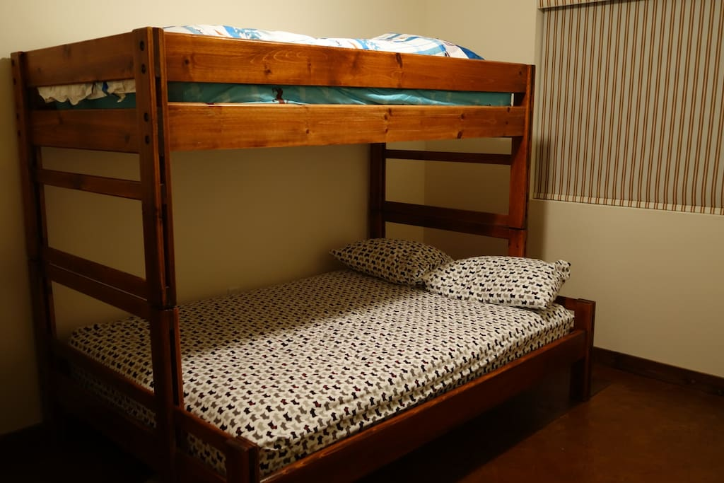 This room has bunk bed with twin and full size mattresses. The other guest room has a queen bed