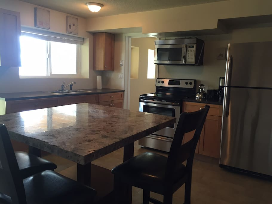 Large bright kitchen with stainless steel appliances and 16 square foot island.