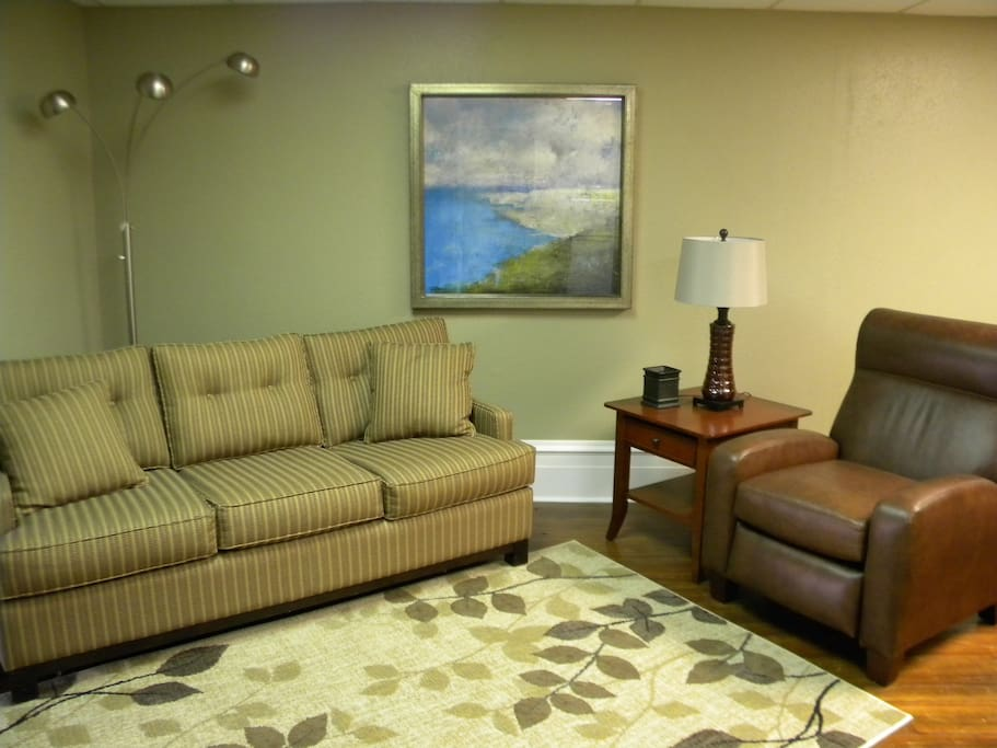 The living room area has a nice couch and reclining chair.