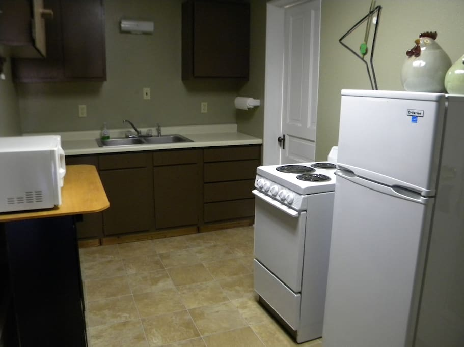 The kitchen features a refrigerator, stove, oven, microwave, and a double sink.