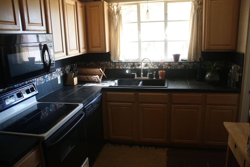 The kitchen has black slate countertops w/mosaic trim and Sonoran style authentic saltillo tiled flooring.