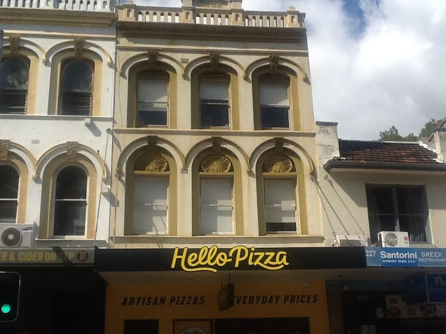 front of the building, property above 'hello pizza'