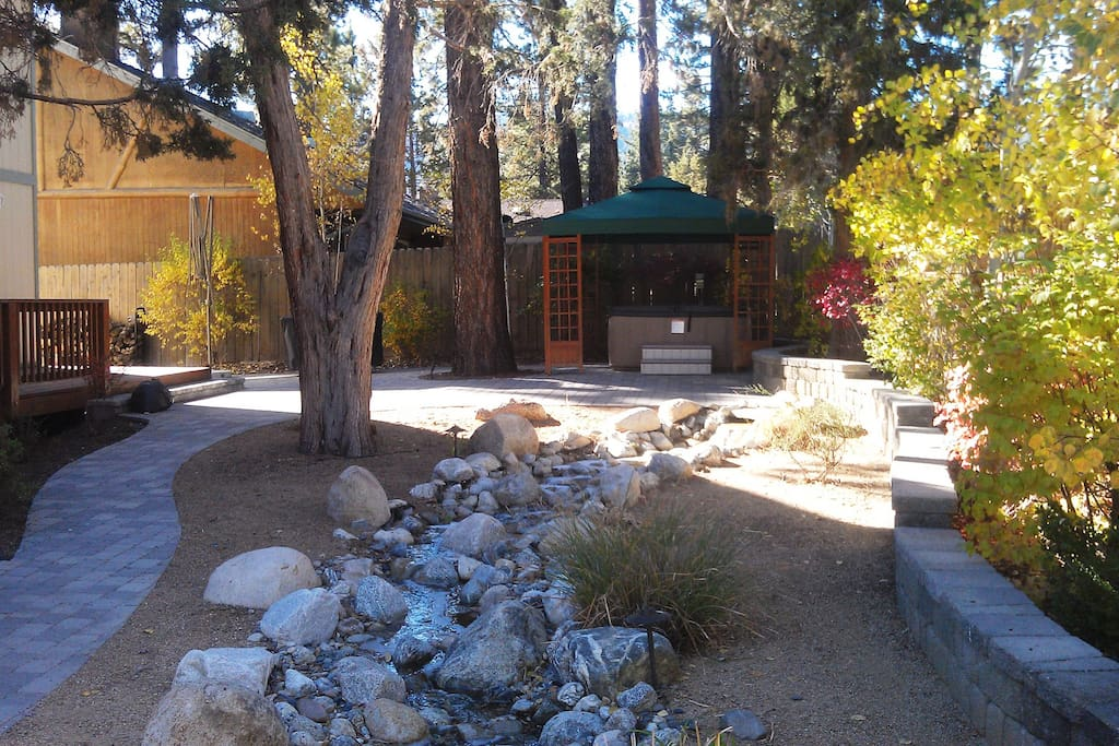 Private rear yard with Jacuzzi, horse shoe pit, fire pit, and rock stream.
