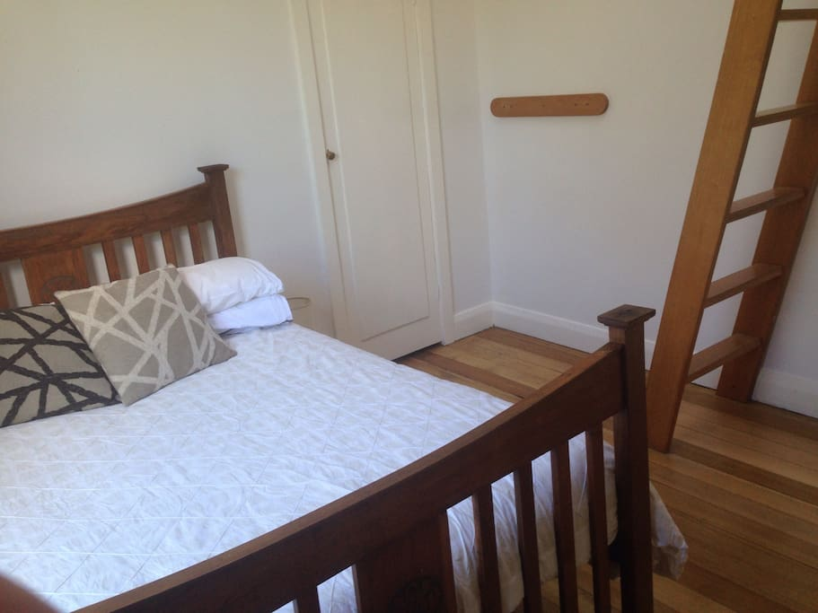 Downstairs bedroom with ladder to loft room with single bed
