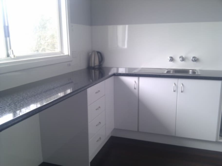 Big kitchen with stove, full sized fridge, microwave and cooking utensils.