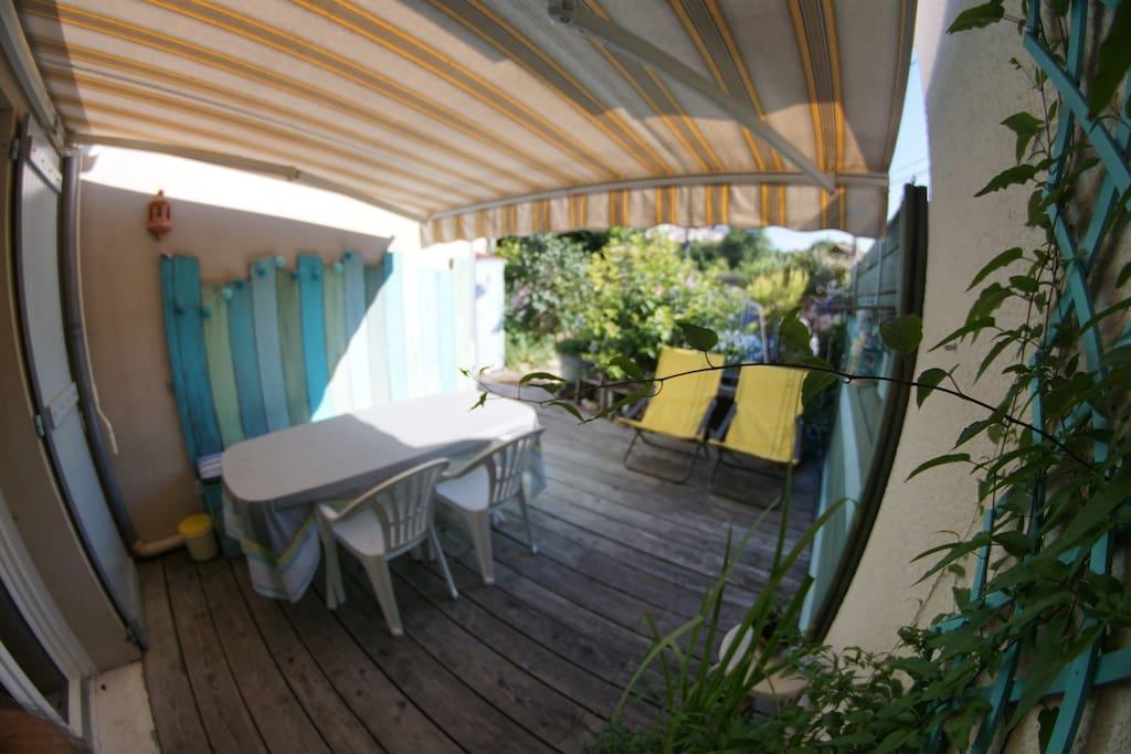 Terrasse sous store - salle à manger extérieure - petit salon