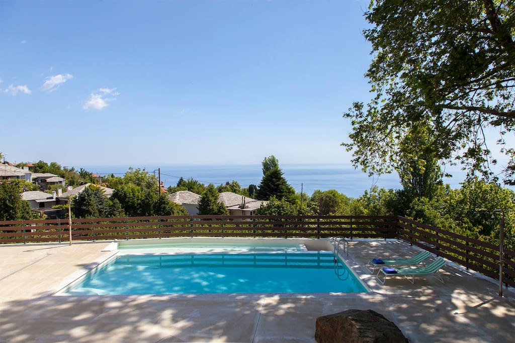 The pool area in front of the villa with the amazing view to the total blue of Aegean Sea!