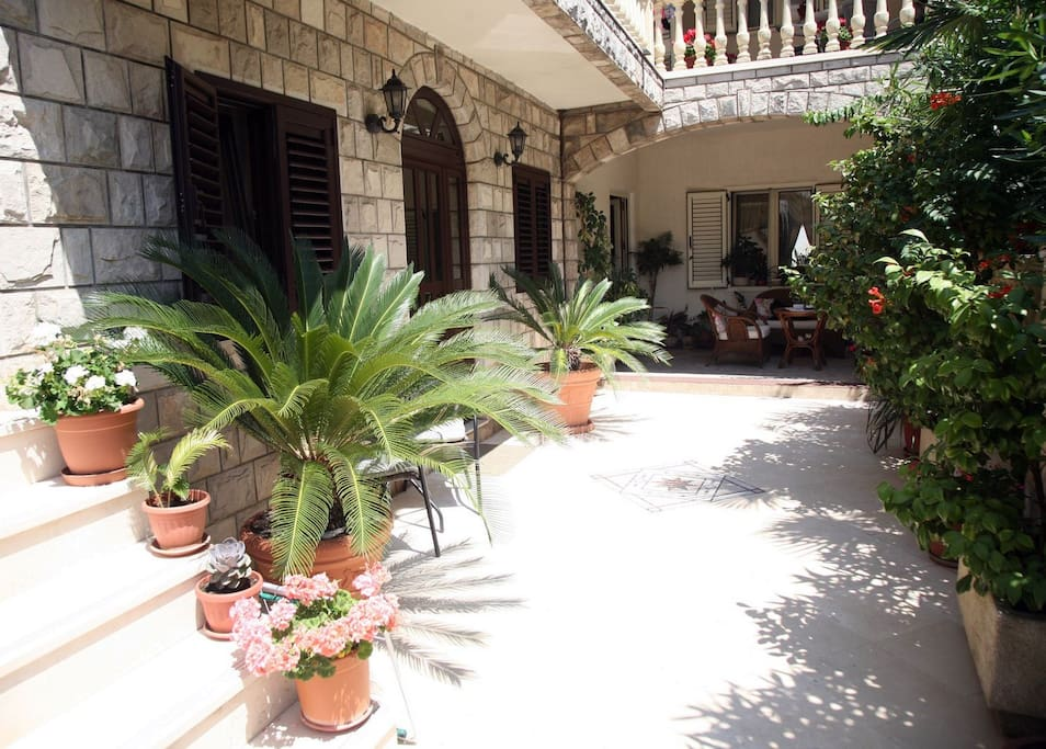 The  entrance to the house has  marble flooring surrounded by a variety of Mediterranean plants.