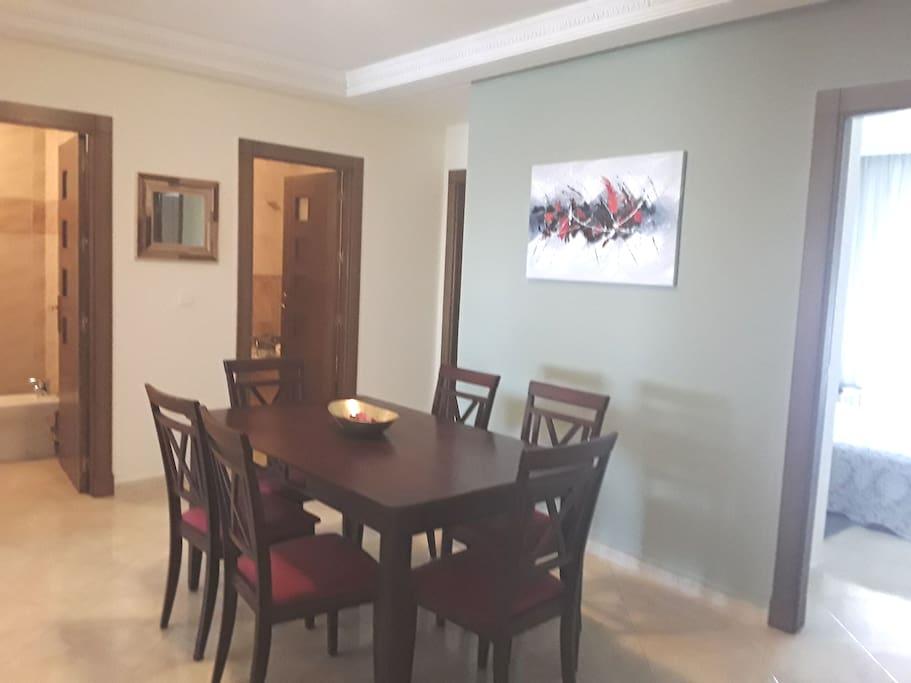 Espace pour manger. Une jolie table en bois massif avec ces 06 chaises en bois tapissé en rouge Bordeaux.