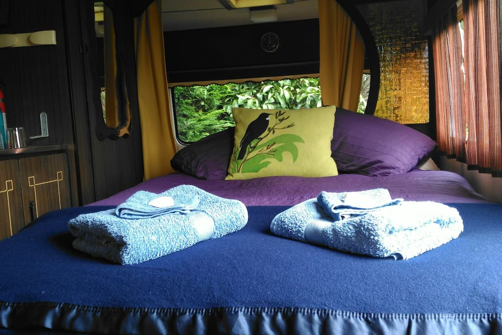 Inside the caravan is a double bed and separate area with table and seating.
