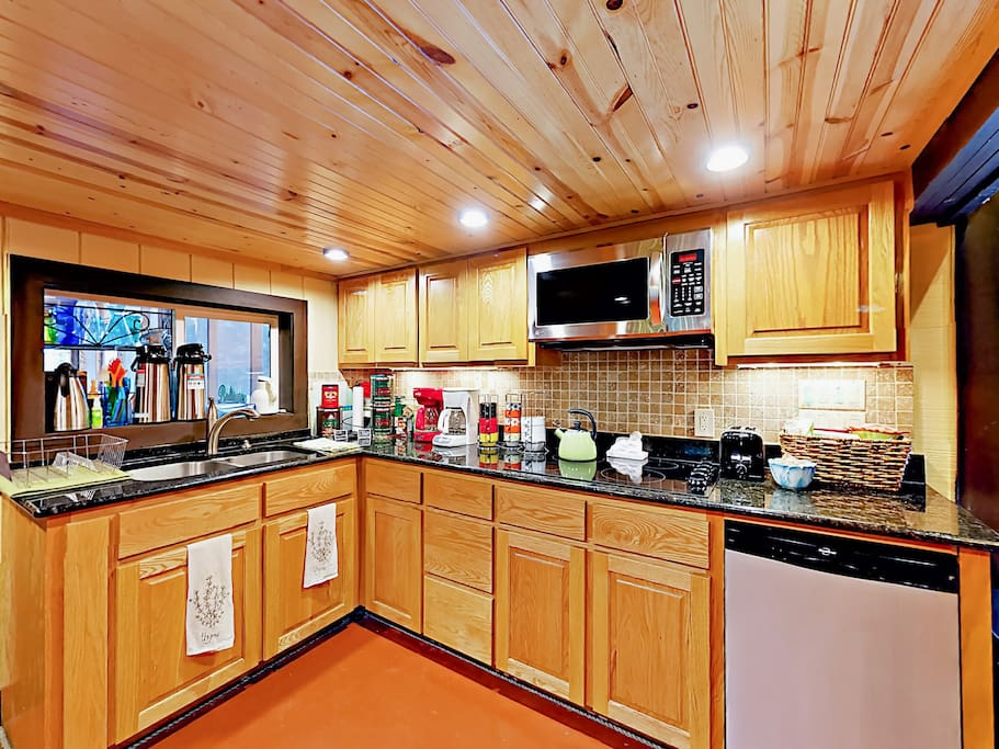 Wood-paneled ceilings and wood cabinetry lend a rustic air in the kitchen.