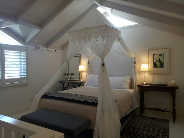 The serene bedroom features a comfortable queen size bed upstairs at The Loft overlooking the private guest garden.