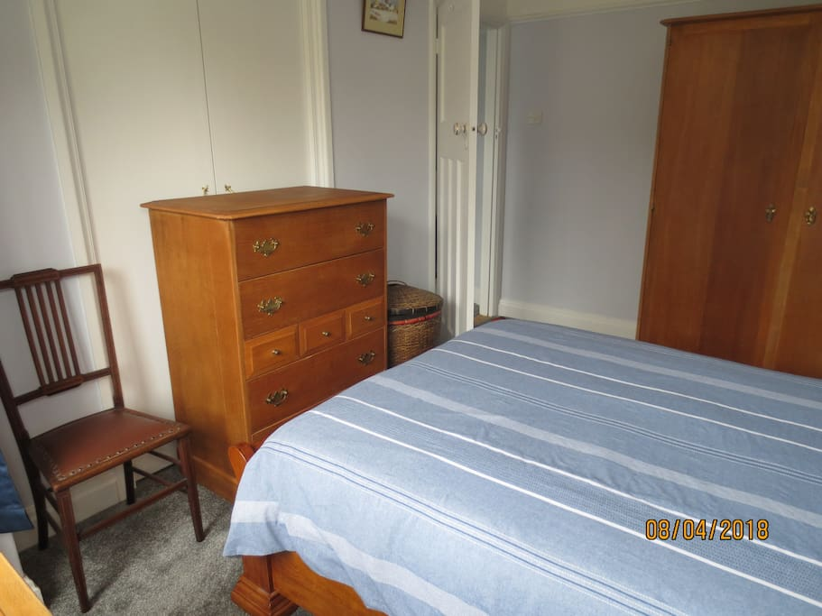 Bedroom 1. Chair, chest of drawers and laundry basket.