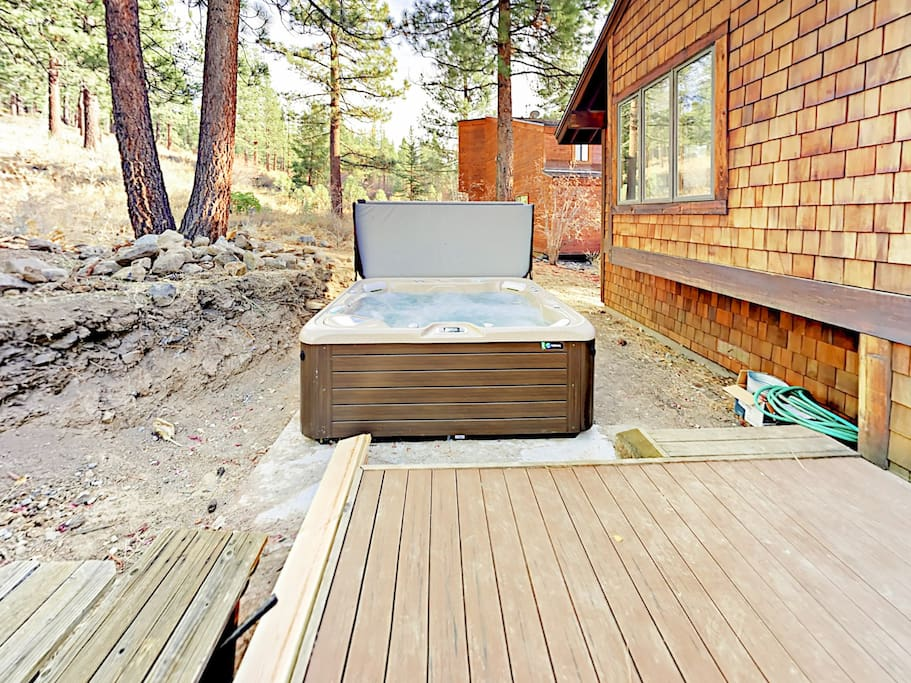 A private deck with a hot tub provides a pleasant spot to relax amidst the surrounding forest.