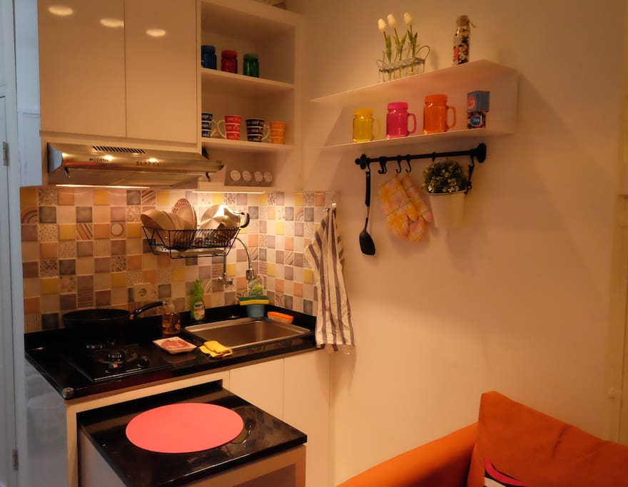 Compact kitchen completed with basic cooking and dining utensils