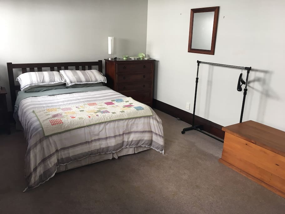 Large double bedroom with clothing rail and chest of drawers and mirror