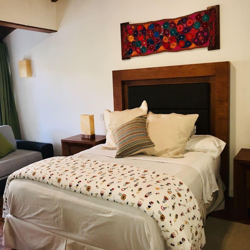 La amplia recamara Lirio esta hermosamente decorada y cuenta con una cama Queen size super cómoda y dos camas individuales.  Lirio Room is a beautifully decorated room with a modern,  and comfortable Queen size bed, and two twin size beds.