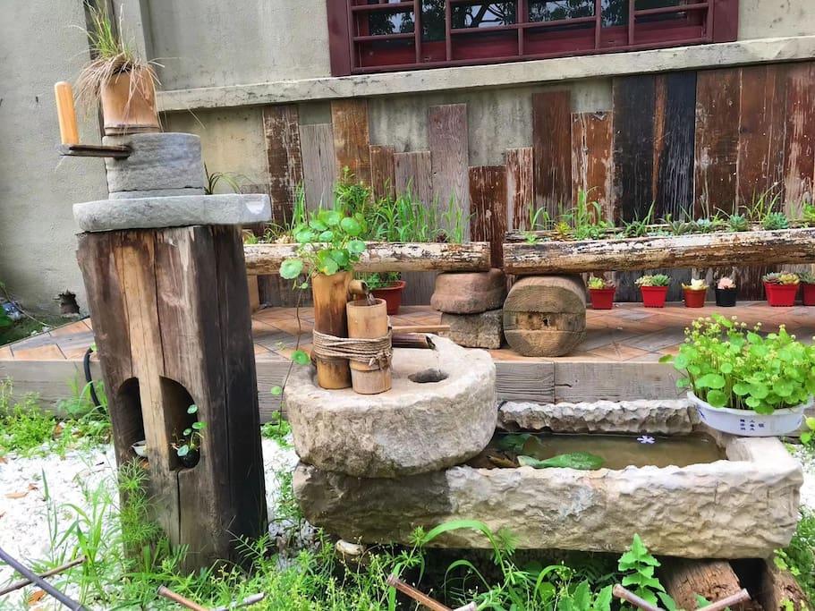 从村子里收来的石磨,猪槽做的流水器,景观