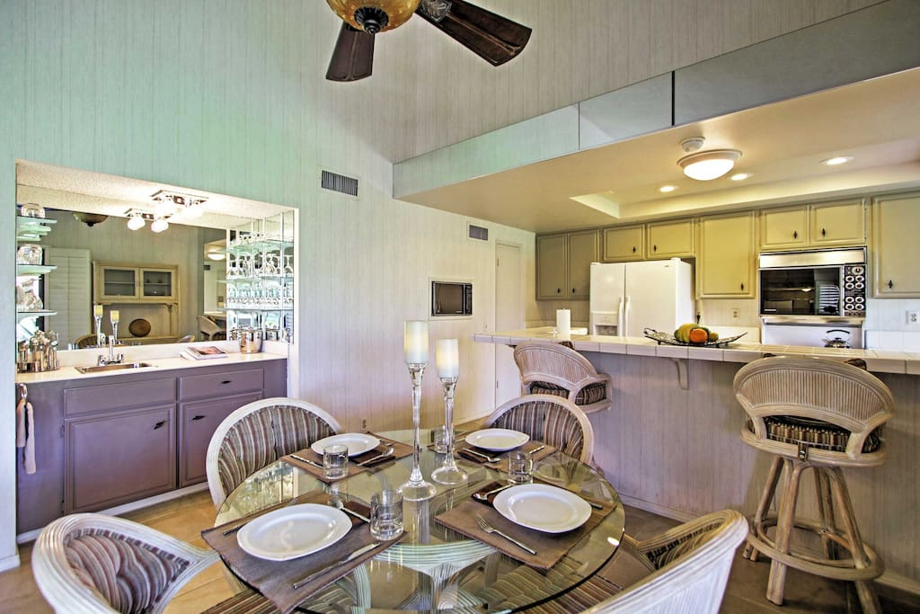 Enjoy a beverage from the wet bar before sitting down at the dining table to feast on a delicious meal.