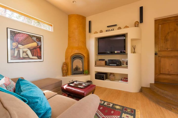Cozy living area with fireplace, flat screen TV, satellite, skylight and ceiling fan in Casa de los Sueños casita