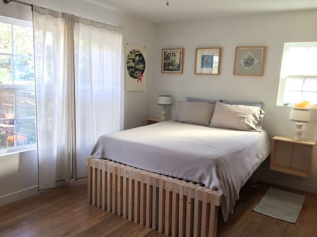 Master bedroom. Queen size mattress (brand new as of May 2017), linen sheets, organic cotton blanket, handcrafted wood bed frame. Natural light, Molekule Air Purifier, original art by local artists.