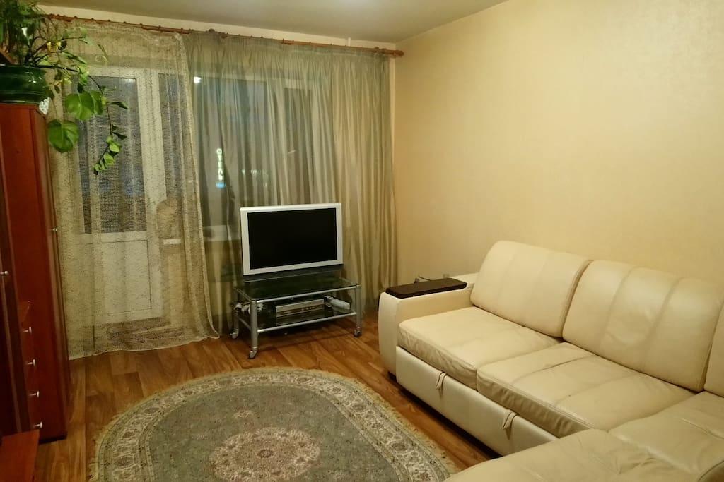 Гостиная, угловой диван-кровать, телевизор, выход на лоджию с дополнительным спальных местом