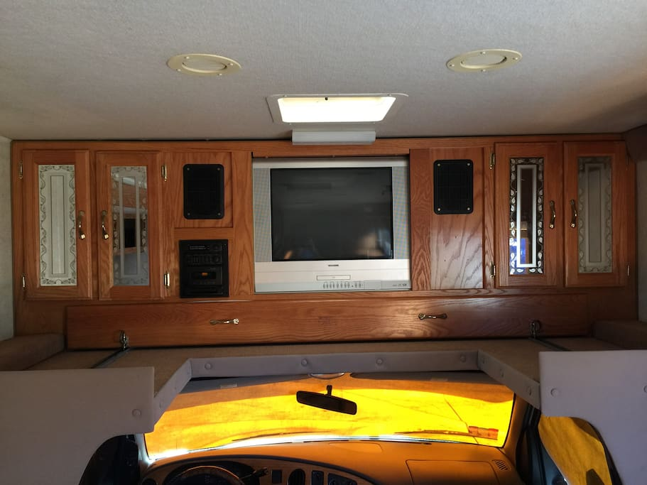 There is a twin bed above the cab (under the TV) for people with longer legs.