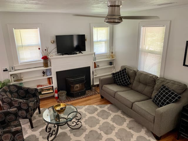 """Living room with wood pellet stove (perfect for winter), original refinished hardwood floors. Have upgraded to a larger 50"""" smart tv since the photo was taking."""