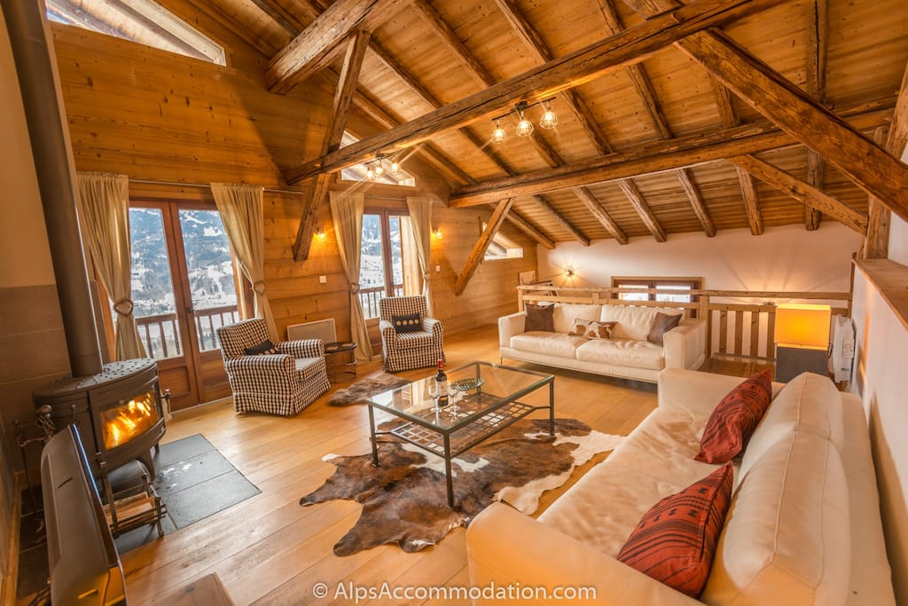 The vast living area features wonderful exposed beams, a cosy log fire, and wide open views