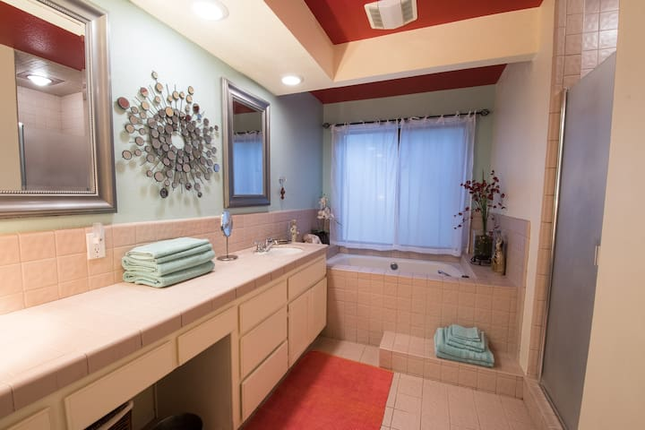 Large bathroom with shower and tub plus separated toilet area for privacy.