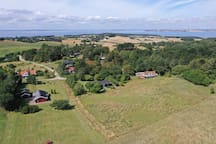 Drone view westwards with Århus in middle of the horizon. The house is red roofed with white balcony (front right).