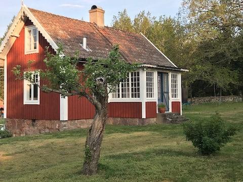 Pieni 1800-luvun talo rauhoittavassa maaseudulla.