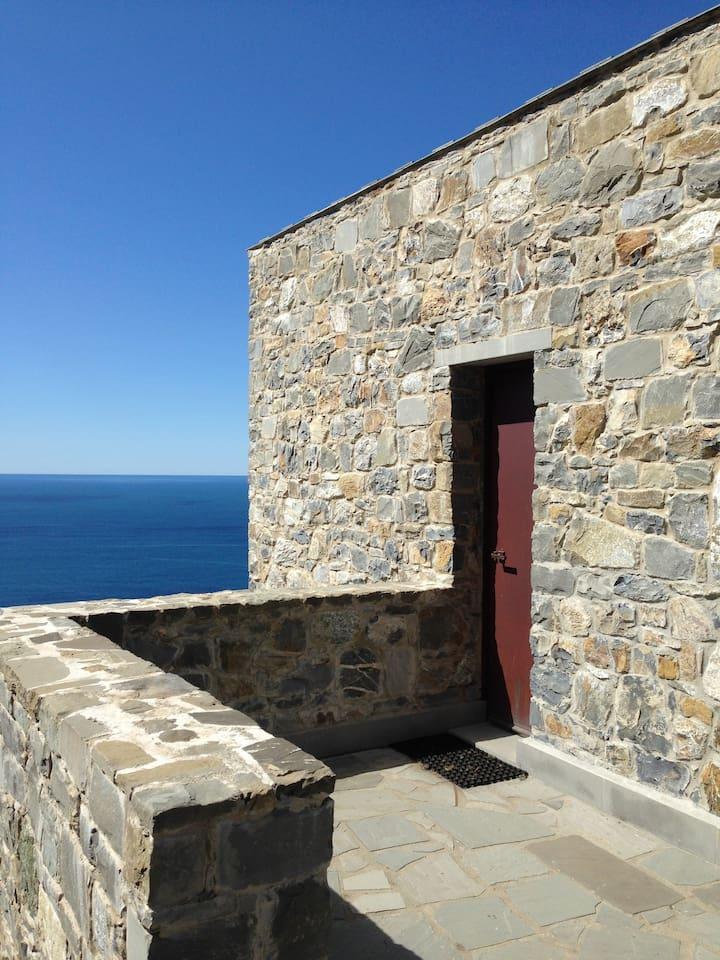 La Torretta in pietra è davanti al mare. The stone turret is in front of the sea.