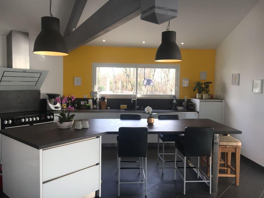 Grande cuisine ouverte avec 4 chaises de bar + 4 tabourets (+3 d'appoint) un grand piano 5 feux induction et ses 2 fours + 1 grill