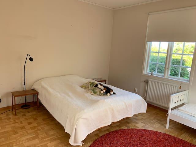 Rum med en dubbelsäng och en barnsäng.