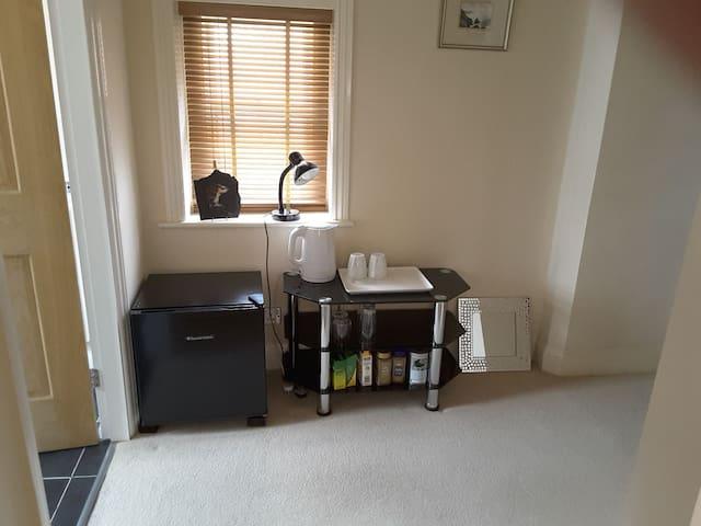 Tea/coffee area with refrigerator on landing between bathroom and bedroom
