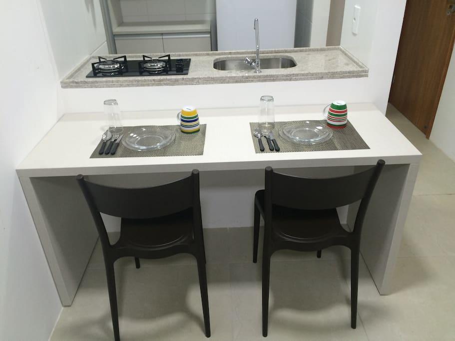 Mesa de jantar e cozinha americana.