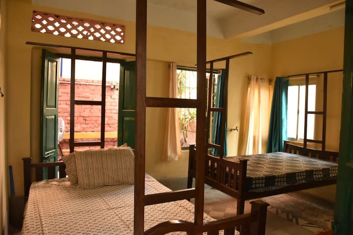 Bedroom 3 : the twin beds with the zamindar-style wooden posters and the well ventilated room , takes you back to the Kolkata of old.