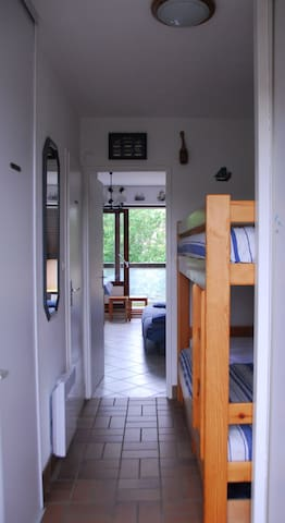 L'entrée avec penderie, 2 lits d'une personne superposés (90 cm) + 2 couettes blanches