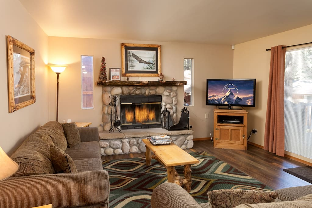Open and Bright Living Area with FlatScreen Cable TV and River Rock log fireplace.