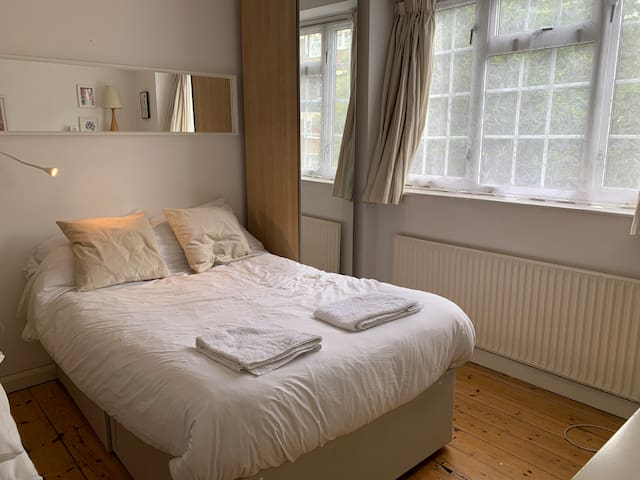 Master bedroom, double bed, reading lamp, black out curtains.