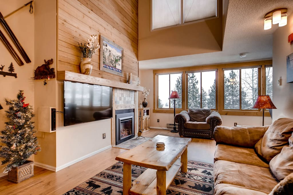 Large bright open living area with newly installed TV and electric fireplace