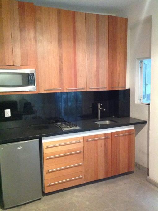 Cocina equipada microondas, refrigerador y estufa, con vasos y platos.