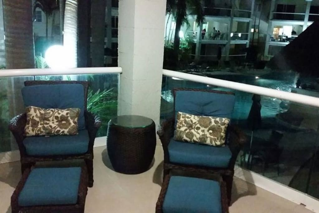 Chairs and view of the pool from the porch.