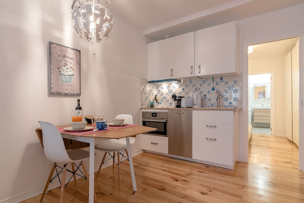 Kitchen space behind the dining table with traditional tiles