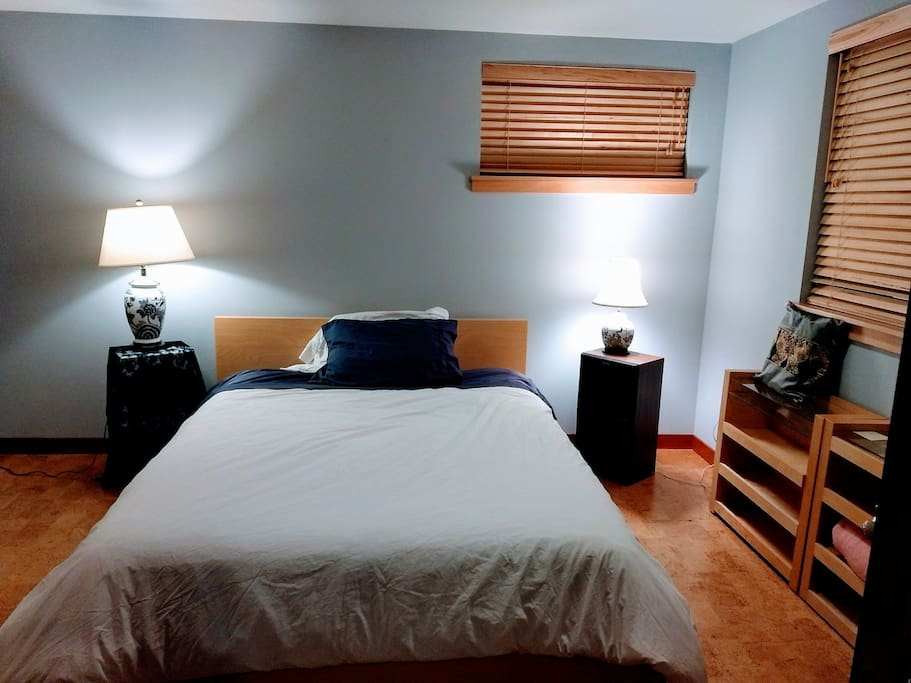 Queen size bed on cork floors with dist more covers on pillows and mattress for people allergic to dust mites.