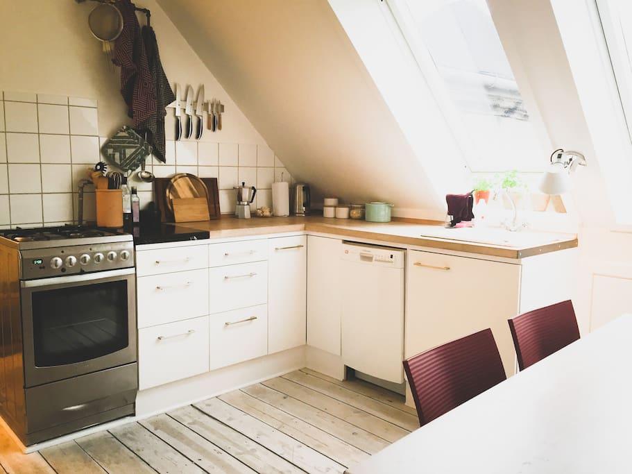 Køkkenbord, komfur og opvaskemaskine, set fra spisebordet.