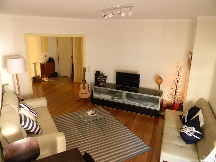 Bright and spacious living area with HD TV and sofa bed.