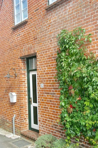 Der Eingang zur Wohnung befindet sich an der linken Hausseite.