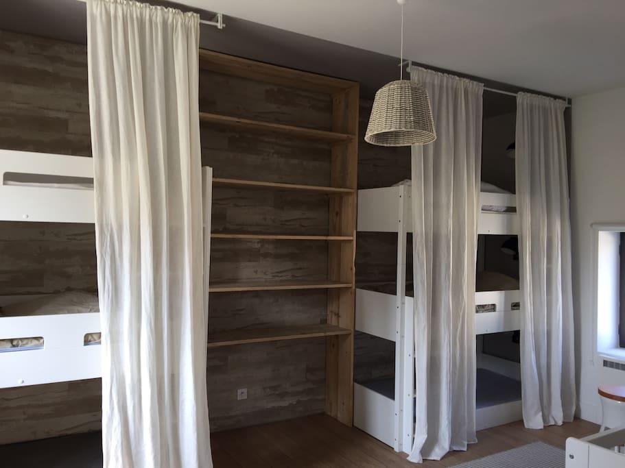 Un dortoir avec 6 lits confortables et petite lumière individuelle pour chaque lit.
